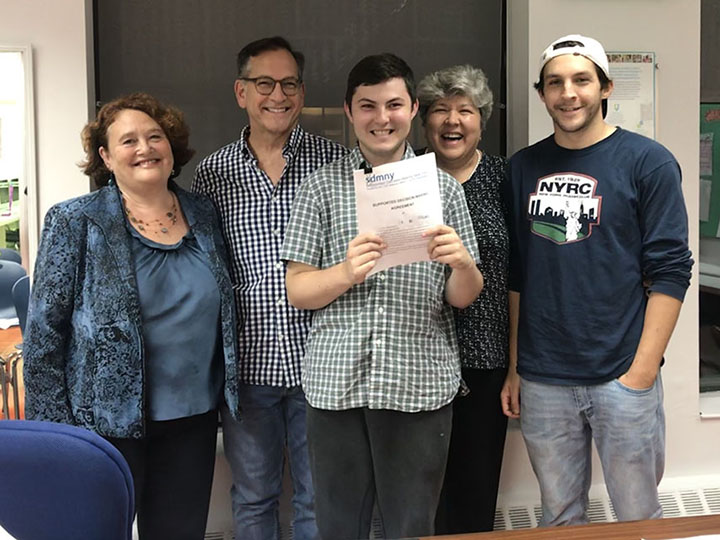 Thomas Gutowski holding his SDMA with family and supporters at his signing ceremony